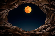 Inside A Mysterious Cave At Night Looking Out To See A Full Moon, A Cave Filled With Rocks.