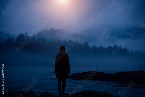 Fototapeta Dark human silhouette in a thick fog against the background of forest, hills and mountain river