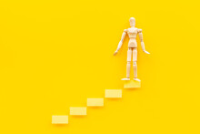 Wooden Man Figure On Stairs. Business Career And Leadership Concept