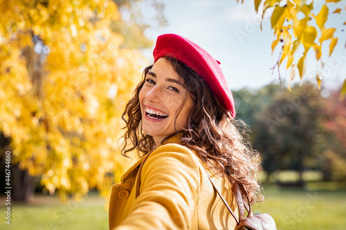 Obraz na plátně Smiling happy woman looking behind in an autumn day