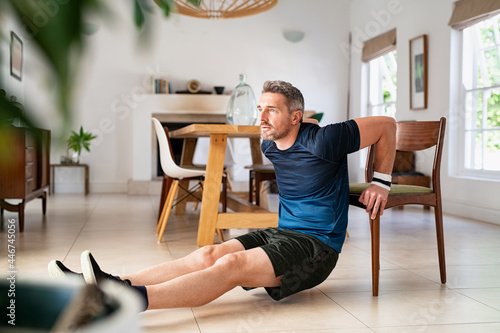Obraz na plátně Mature man doing triceps dips using chair at home