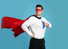 Businessman In Superhero Cape And Mask Taking Shirt Off On Light Blue Background