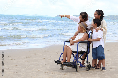 Fotografia Happy disabled senior elderly woman in wheelchair spending time together with her family on tropical beach