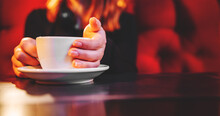 Woman Hands Holding A White Cup Of Tea Or Coffee Standing On The Table In Cafe