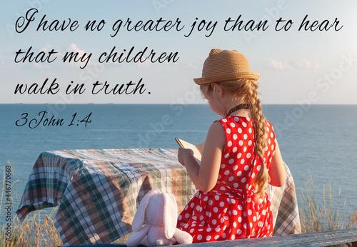 Little girl reading Bible on sea background Fototapete
