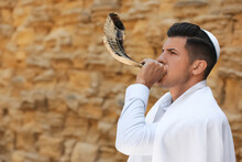 Jewish Man In Kippah And Tallit Blowing Shofar Outdoors. Rosh Hashanah Celebration