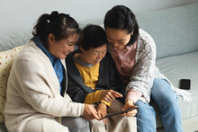 Happy Senior Asian Woman At Home With Adult Daughter And Granddaughter Using Tablet