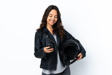 Young Woman Holding A Motorcycle Helmet Over Isolated White Background Holding Coffee To Take Away And A Mobile