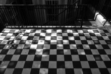 Black And White Image Of Checkered Pattern Floor. Wrought Iron Fence And Staircase In The Background.