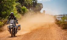Man Riding His Adventure Motorbike On Dusty Road In Cambodia