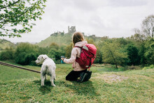 Girl Sat With Her Dog Looking At A Castle In The English Countryside