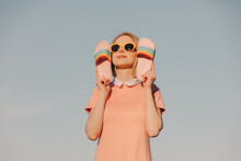 Style Woman In Pink Dress With Yellow Glasses Hold Shoes On Blue