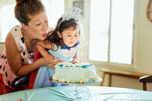 Mother And Daughter Blowing Candles On Birthday Cake At Home