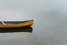 Empty Yellow Canoe At A Wooden Dock On A Calm Lake In Canada.