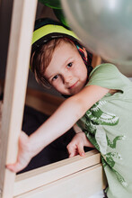 5 Years Boy Playing In His Room, Wearing Green T-shirt With Dinosaurus Print And Dino Helmet
