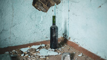 A Dusty, Dirty Open Bottle Of Wine Stands In The Corner Of An Old Room Against The Blue Wall. Abandoned Country House, Old Plaster And Bricks Broken And Crumbling. Vintage Still Life, Film Effect