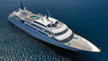 Aerial Drone Photo Of Luxury Mega Yacht With Wooden Deck And Pool Facilities Anchored In Mediterranean Open Ocean Deep Blue Bay