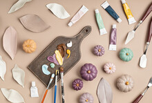 Hobby Background With Handmade Clay Leaves And Pumpkins, Paint Brushes And Art Accessories. DIY, Craft Decoration For Fall Holidays. Flat Lay, Top View