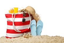 Stylish Bag With Beach Accessories On Sand Against White Background