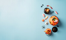 Various Halloween Sweets And Candies In A Pumpkin Pot Top View On Blue Solid Background With Copy Space