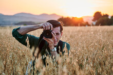 Portrait Of A Photographer Looking At Camera In A Meadow At Sunset