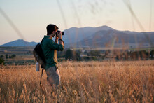 Man Photographer With A Backpack Takes A Photo In A Meadow At Sunset