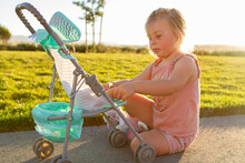 Young Toddler Girl Playing With Toy Stroller At The Park During Sunset