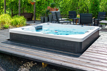 Large Hot Tub Embedded In The Backyard Terrace. A Sunny Summer's Day In The Shelter Of A Green Garden. Everyday Luxury And Relaxation In Your Own Backyard. Spa Complex, Vacation And Traveling Concept.