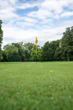 Golf Hole With A Yellow Flag In The Middle Of An Empty Golf Course And Perfectly Cut Grass