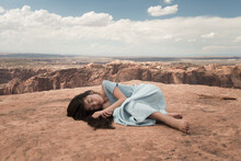 Asian Girl In Blue Dress Laying Down And Dreaming On Edge Of Crater On Red Soail In Canyonlands National Park, USA