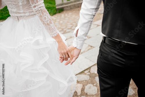 Billede på lærred The bride and groom hold hands
