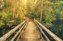 Wooden Bridge Over Dark Water River Towards Forest And Bright Sun