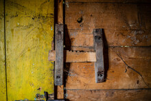 Old Wood Latch On The Barn Door. Fasteners On Rusty Nails, Notched Bolt Bar. Vintage Retro Rustic Interior Of An Ancient Hut, Log Walls Of Natural And Yellow Planks. Covered In Cobwebs, Dirt And Dust.