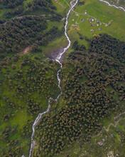 Tolle Drohneaufnahmen In Den Schweizer Alpen. Wundervolle Grüne Bäume Und Ein Mächtiger Wasserfall In Mitten Des Waldes. Vogelperspektive.