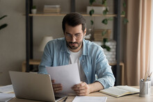 Serious Businessman In Glasses Sit At Workplace Homeoffice Desk Reading Contract Seated At Workplace Desk, Considering Post Paperwork Learns Letter Correspondence News Looking Pensive And Thoughtful