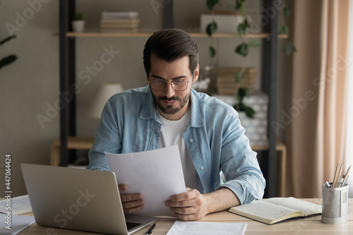 Fotografía Serious businessman in glasses sit at workplace homeoffice desk reading contract