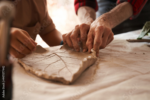 Obraz na plátně Sculptor shapes a clay plate while working at the master class for people