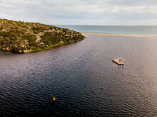 Horizontal Photo Of An Island And The Ocean With Three People Standing On A Floating Wooden Raft