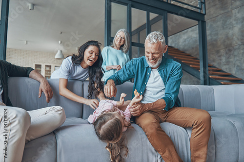 Fototapeta premium Happy family spending time together and smiling while sitting on the sofa at home