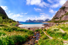 The Concept Of Outdoor Recreation. Beautiful Landscape With A Lonely Tent Near The Sandy Beach Hidden Between High Mountains Among Blooming Flowers And A Clean Stream On The Shore Of The Blue Bay.