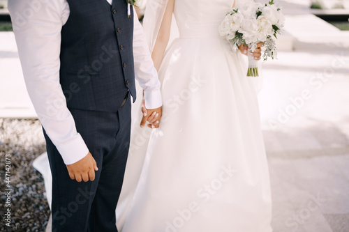 Fotografering Groom holds the hand of bride in a white dress with a bouquet of flowers