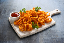 Spicy Curly Fries With Ketchup On White Wooden Board