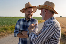 Two Farmers Standing On Road Next To Field Talking Laughing.