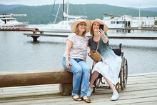 Woman In A Wheelchair Taking A Selfie With Her Friend Against The Background Of The Pier With Yachts, Catamarans