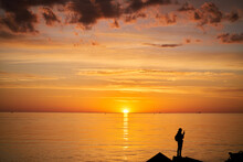 Woman Or Man Standing On Rock Looking Straight. Nature And Beauty Concept. Orange Sundown. Girl Silhuette At Sunset.