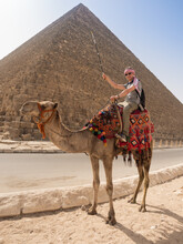 A Tourist On A Camel Poses Against The Backdrop Of The Pyramids In Giza, Cairo, Egypt. Kufiya Is Wrapped Around The Man's Head. The Camel Stands In Full Growth.