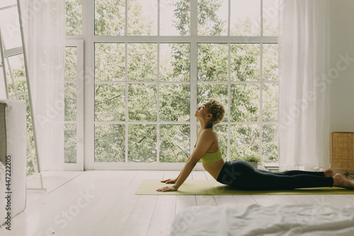 Canvas Print Concentrated black woman practicing yoga in light room with big windows