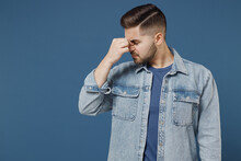 Tired Exhausted Sad Young Brunet Man 20s Wear Denim Jacket Keep Eyes Closed Rub Put Hand On Nose Isolated On Dark Blue Background Studio Portrait. Healthy Lifestyle Ill Sick Disease Treatment Concept