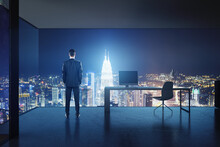 Success Concept With Businessman Back View In High Floor Stylish Office With Night City Skyscrapers View Through Mesh Walls.