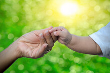 Baby Holds His Mother's Hand, Mother And Daughter Are Holding Their Hands On Green Nature Blurred Background.